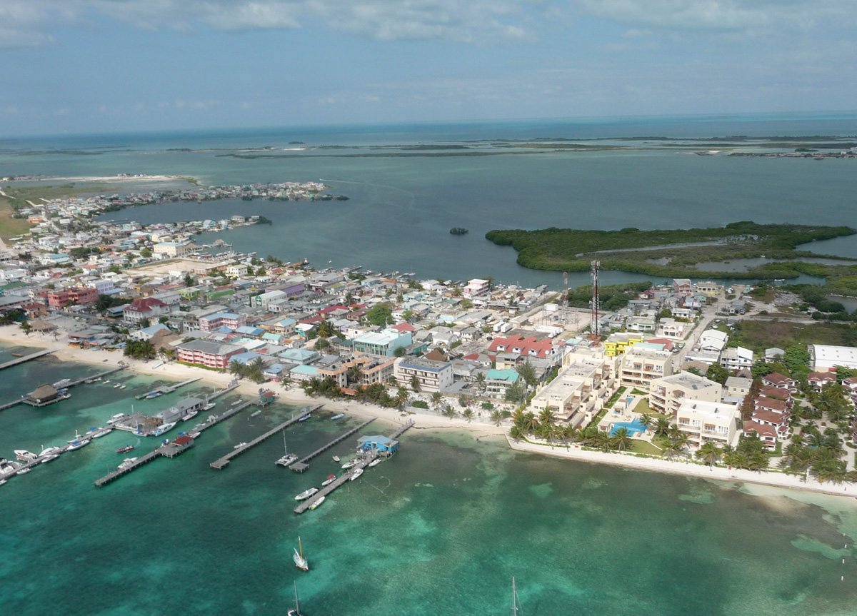 aerial view of boats and houses on narrow stretch of beach in belize
