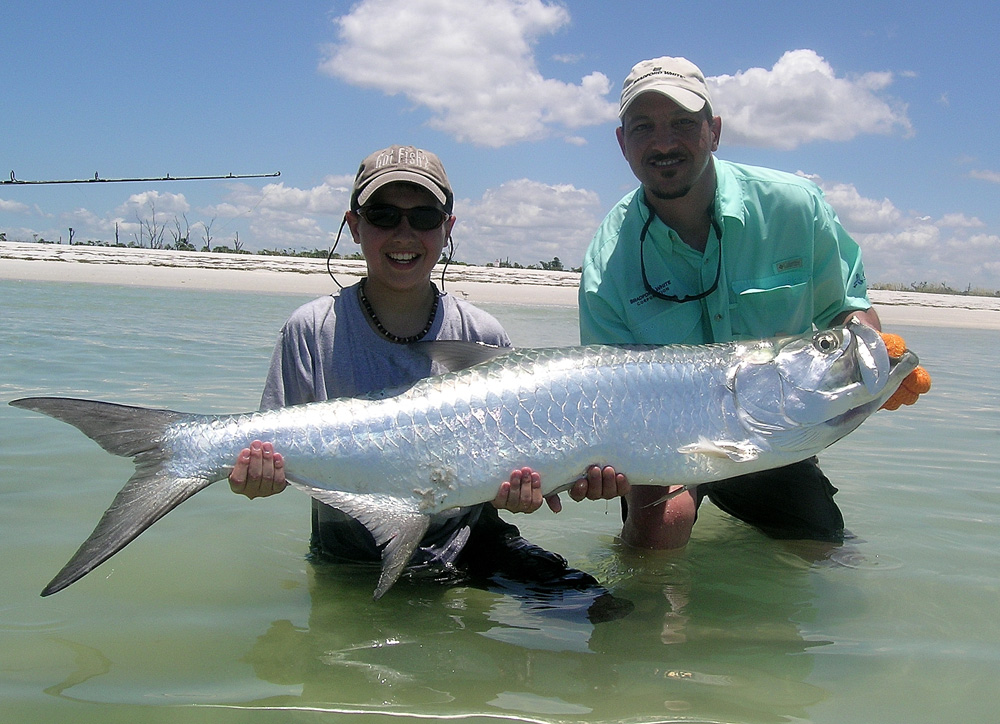 boy holding tarpon after fishing shallows in belize