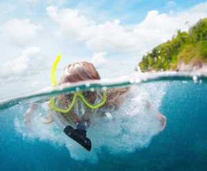 close up of woman snorkeling in blue green waters near remote island