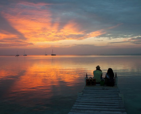 couple enjoying sunset over water on dock with cocktails in belize