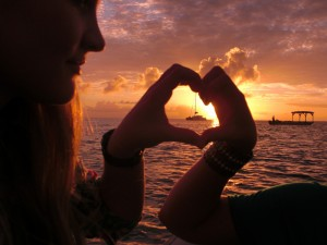 couple form heart hands around luxury catamaran in sunset on island in belize