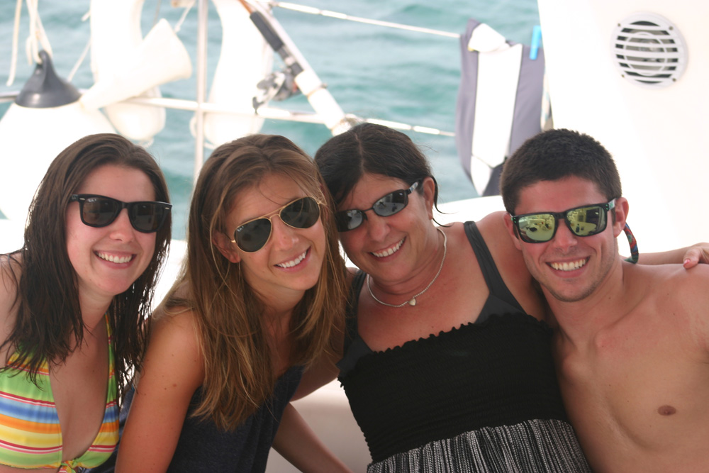 family and friends pose on catamaran charter in beautiful belize