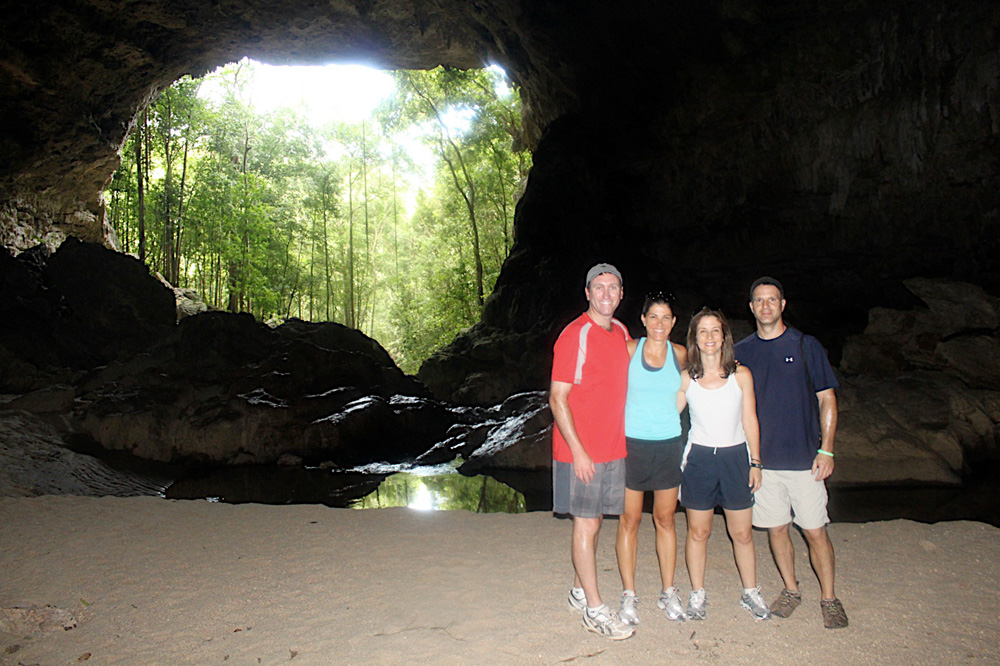 family posting at entrance of cave in belize while on guided cave exploration