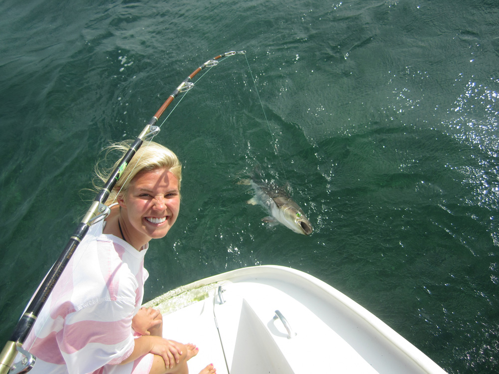 girl poses with fish caught off 50' catamaran sailing in belize