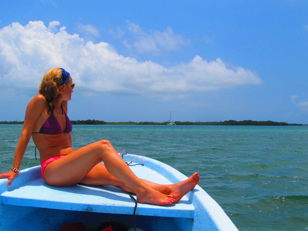 girl riding boat to luxury catamaran while on charter in belize