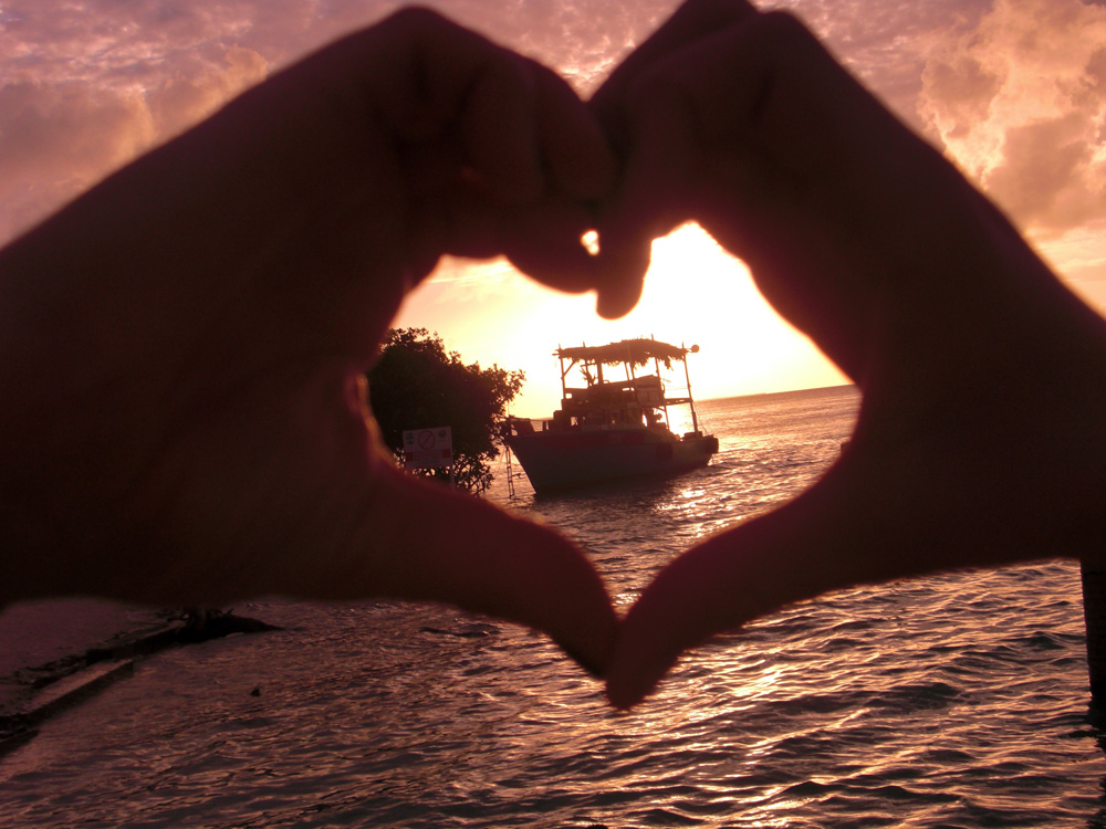 heart hands around boat at sunset near remote island in belize