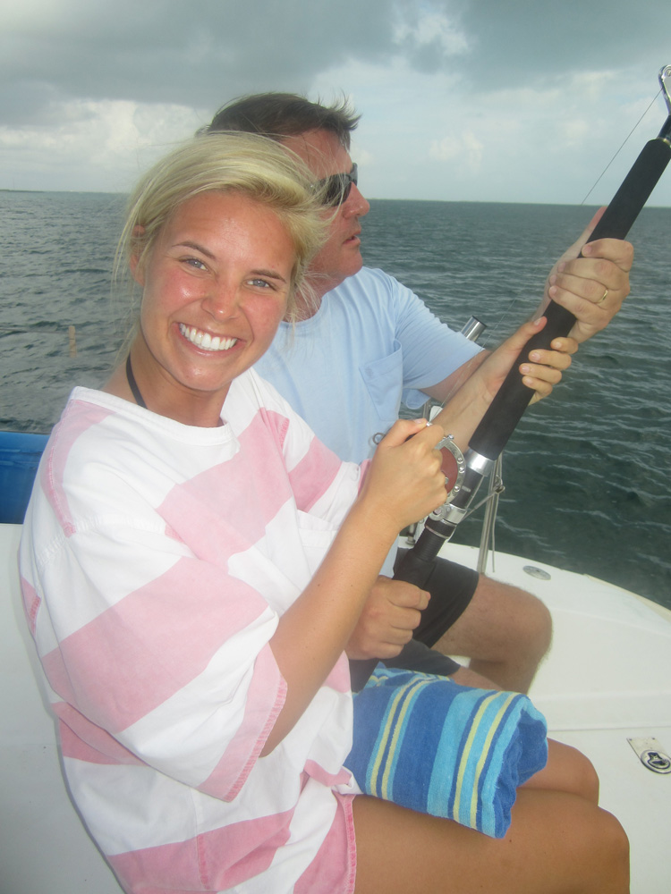 husband and wife fishing off catamaran while on family vacation with belize sailing vacations