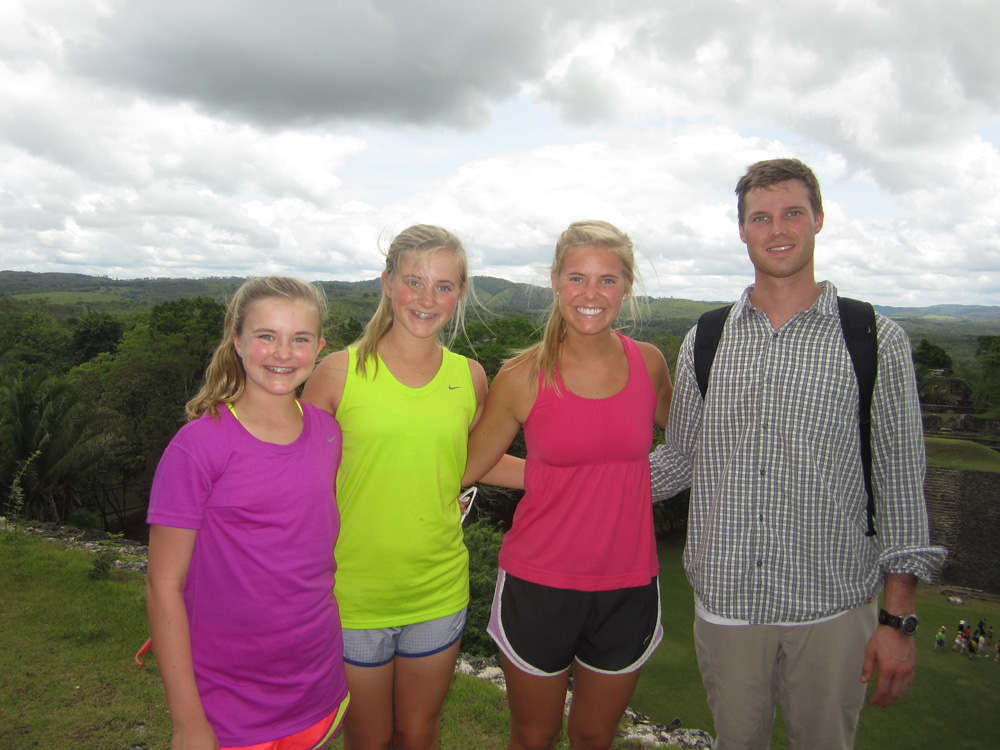 kids and family pose on top of mayan temple with vast jungle on horizon