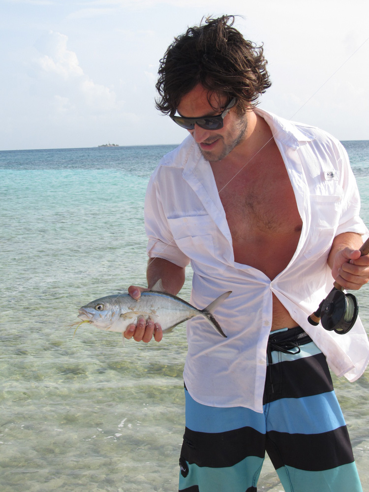 man holding fish caught fly fishing in belize off goff's caye