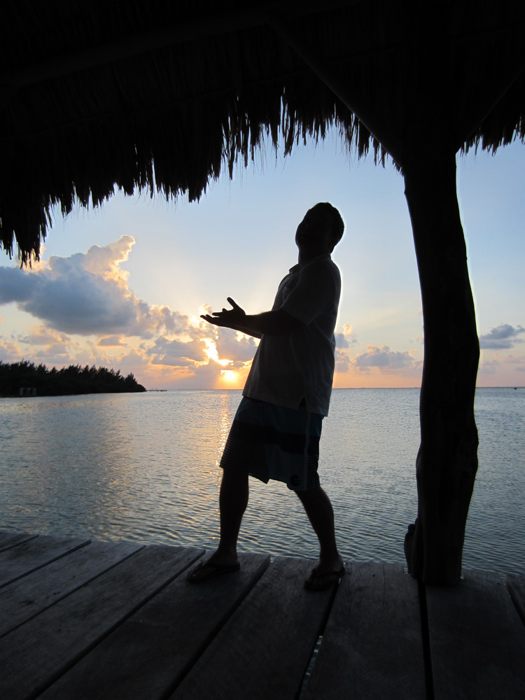 man silhouette pointing to amazing sunset on remote island reef in belize