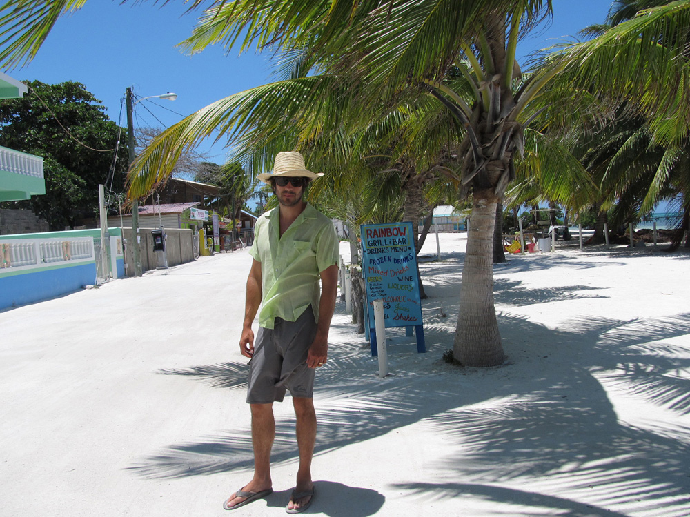 man walking white sand street on belize island near shops