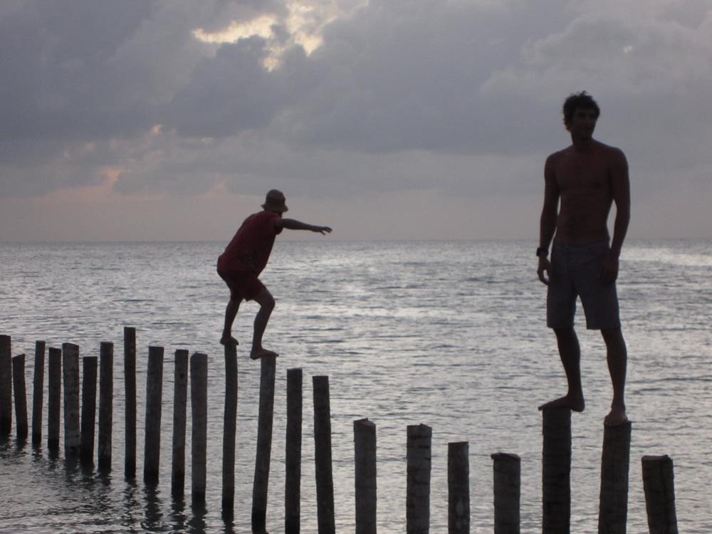 men walking on dock poles near sunset in belize