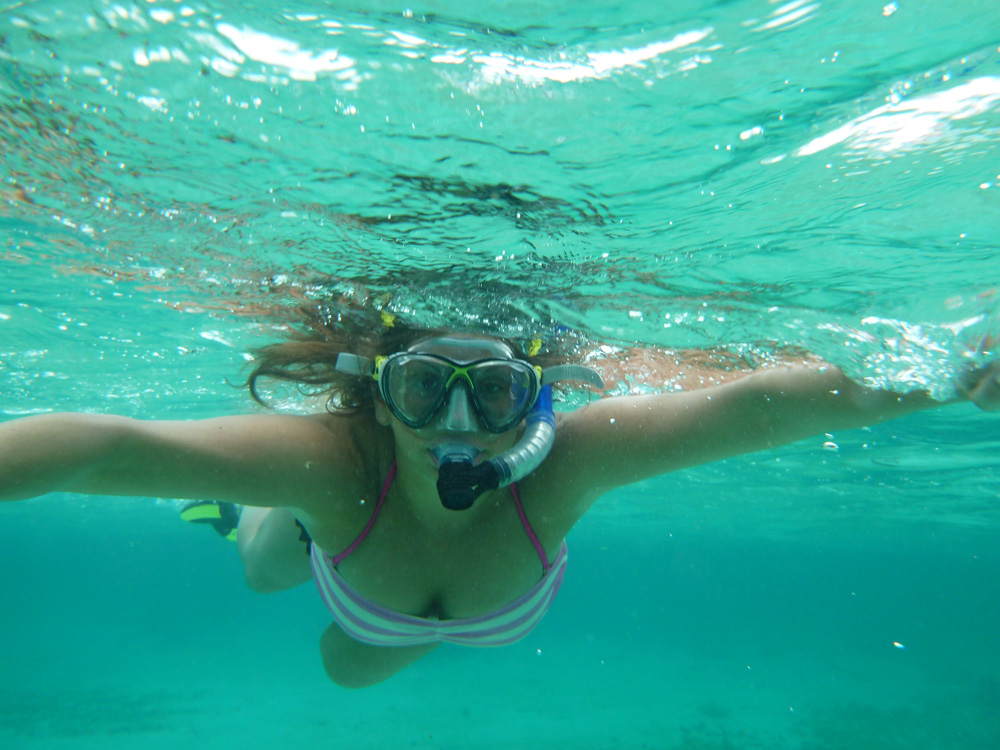 snorkeling girl in belize's clear water shallows