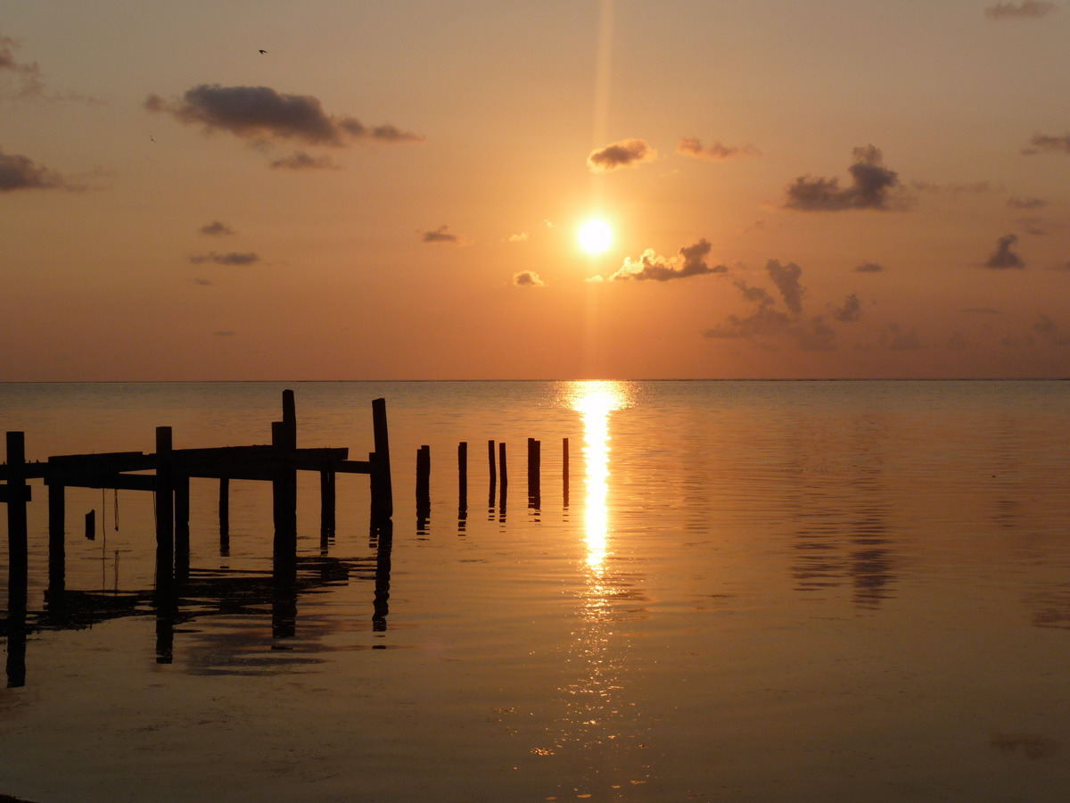 sunset over water and silhouette of dock in belize