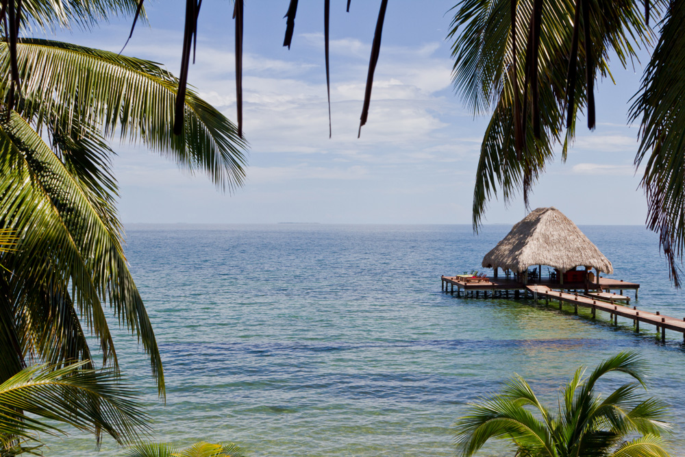 view of tropical paradise and long dock with shaded hut in water
