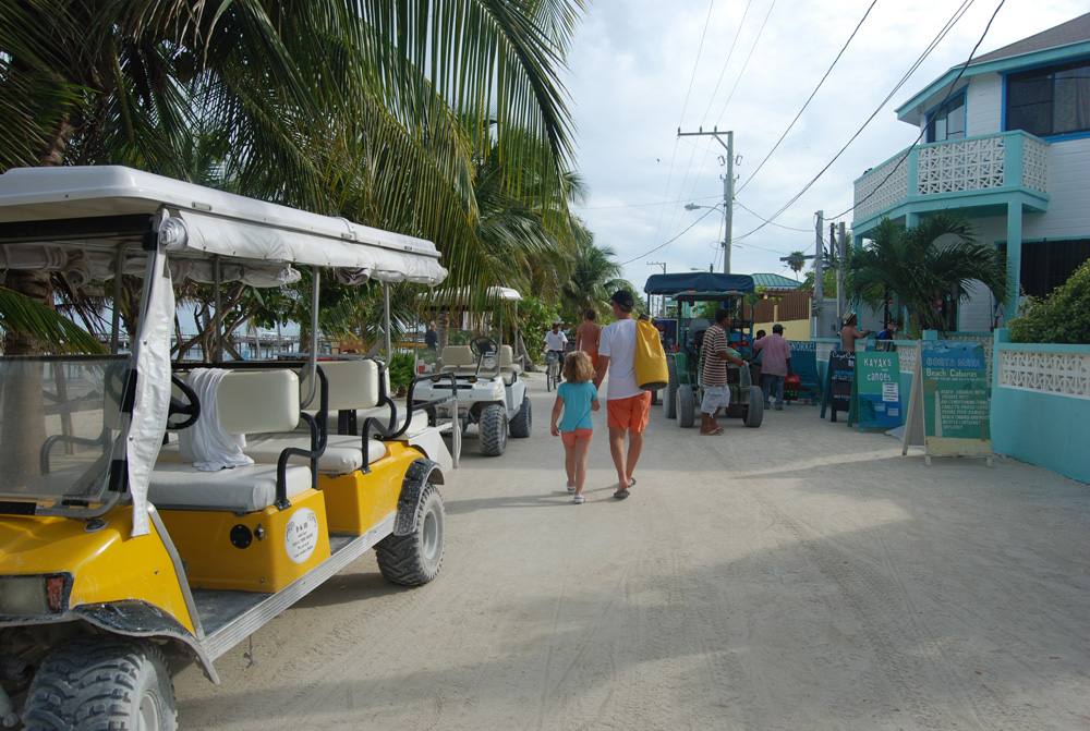 walking with family on white sand streets near shops and golf carts in belize