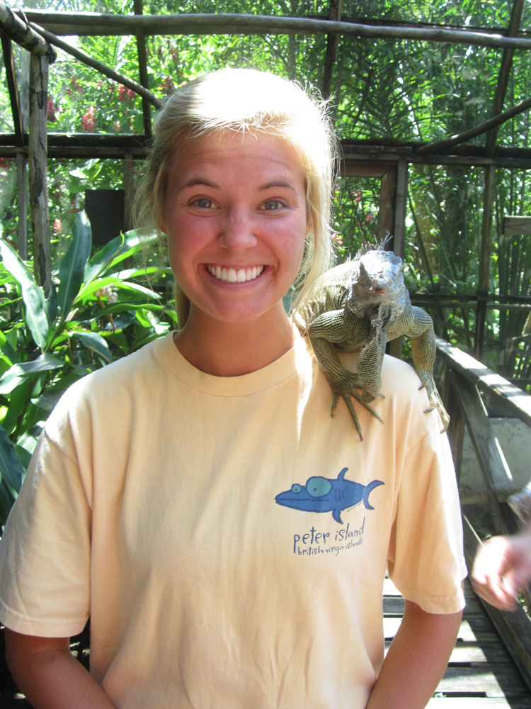 woman poses with large green iguana on shoulder